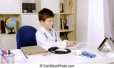 Happy kid doctor working at computer in medical office