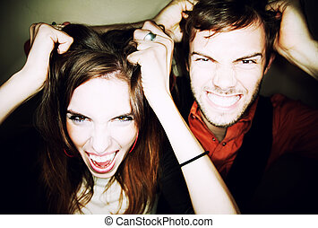 Couple tearing out their hair - Crazy young couple pulling...