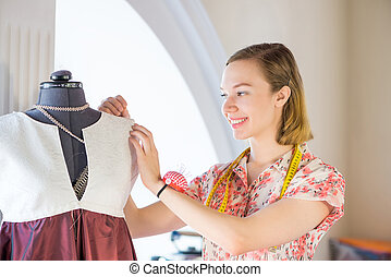 Atelier worker - Young pretty needlewoman fitting dress on...