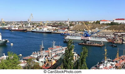 Two ships tow the crane on the sea gulf. Sevastopol - nonfreezing sea trade and fish port in the Crimea