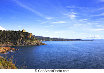 Cliff rock and building on the sea on sunset. Quercianella,...