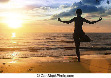 Silhouette of woman practicing yoga during amazing sunset at the seaside.