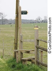 footpath and stile across field Country Stile. Overgrown...