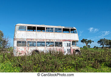 Rusty Abandoned Double-Decker Bus Standing in a Field, sunny...
