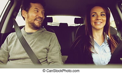 Beautiful couple driving car smiling - Happy people in...