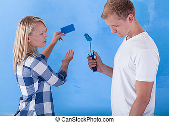 Man painting wall for bad colour and unsatisfied girl