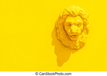 Lion head statue on yellow background