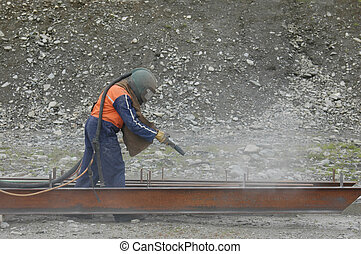 sandblasting 1 - man sandblasting I-beam in preparation for...