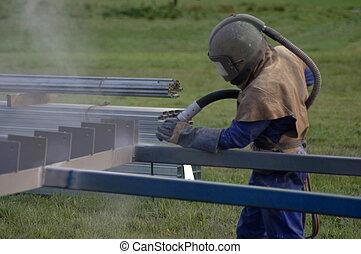sandblaster at work - tradesman sandblasting beams for...