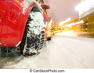 car with winter tyre - Studded tyre of red car on street in...