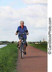 Senior Dutch lady on bike. - Seventy year old lady riding a...