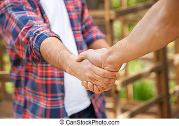 Construction Workers Shaking Hands At Site - Cropped image...