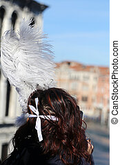 masked girl with big feathers over rialto bridge in venice
