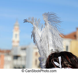 masked girl with big feathers over rialto bridge in venice...