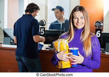 Woman Holding Snacks While Man Buying Tickets At Box Office