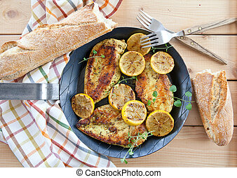 Marinated chicken breast with organic lemon in iron pan