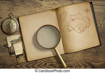 Adventure and travel nautical theme. Diary with map and magnifying glass on wooden table.