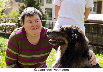 disabled woman is caress a dog - mentally disabled woman is...