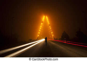 silhouette on the bridge in the night with cars movings