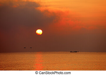 fisherman boat in the sunrise on the sea with birds flying