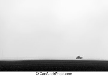 Single tractor on the field black and white
