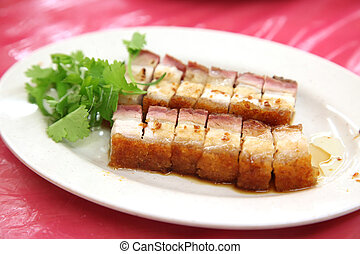 Chinese roast pork with crispy skin, sliced on plate