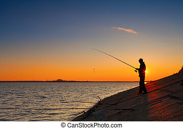 Silhouette of fisherman fishes on river bank against a...