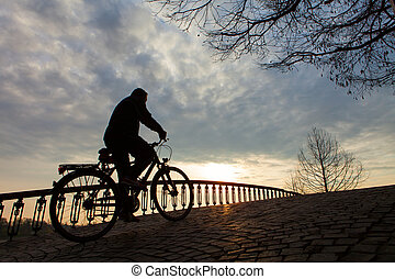 Silhouette of a man on muontain-bike, sunrise