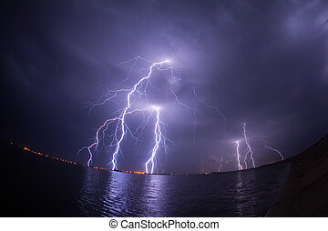 Thunderstorm and lightnings in night over a lake with...