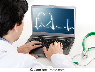 doctor working on laptop with heart rhythm ekg on screen