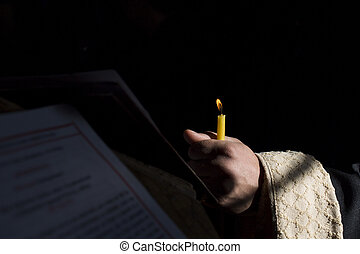 Church candle in hand with book