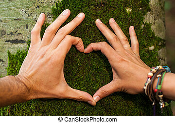 Heart hand on tree with moss by man and woman, loving the...