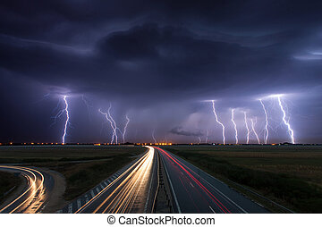 Thunderstorm and lightnings in night over a highway with car...