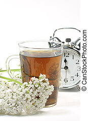 Valerian tea - Herbal tea in a glass with valerian blossoms...