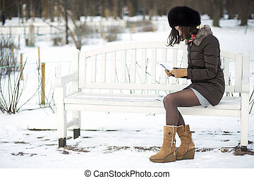 Young woman reading old letters - Lady on a bench sits...