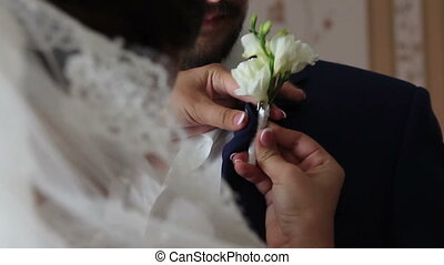 Bride attaches groom's boutonniere with a small pin