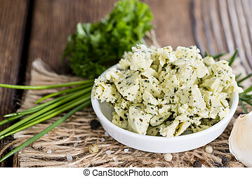 Herb Butter close-up shot in a bowl on wooden background