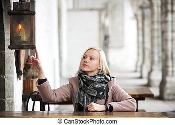Woman dangerously touching the lantern - Blonde with a short...
