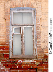 Weathered wooden window on brick wall