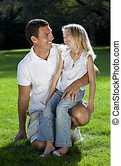 Father With Daughter On Knee Smiling In A Park