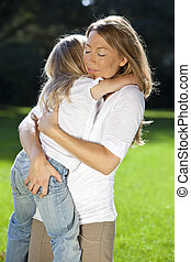 Mother and Daughter Cuddling In A Park