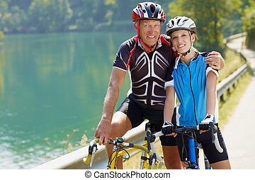 senior cyclist - Senior man and young woman on road bike....