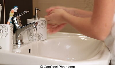 Child washing her hands in the bathroom. Learning good...