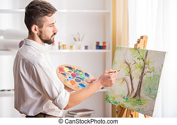 Artist - Side view of highly gifted painter while he is...