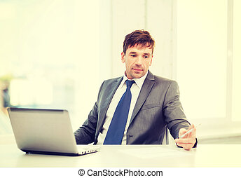 businessman with laptop computer and documents - technology,...