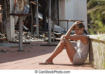 sad woman and burned out house - sad woman sitting in front...