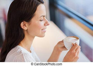 smiling young woman drinking coffee at cafe - leisure,...