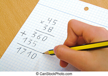 Child doing a math multiplication at school. - Child doing a...