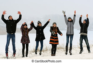 happy young people jumping  in winter