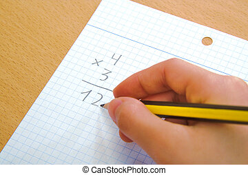 Child doing a math multiplication as homework. - Child doing...